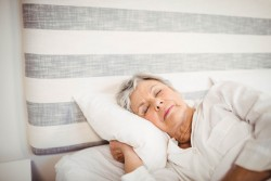 52768102 - senior woman sleeping on bed in bedroom