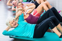 37846893 - group of senior people and young woman and men in fitness gym doing sit-ups on the floor