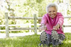 senior woman stretching legs on the grass