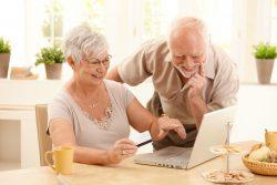 happy senior couple looking at computer
