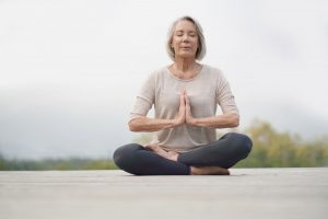 Woman meditating and practicing mindfulness outdoors.