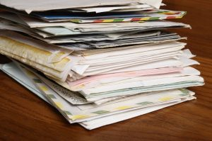 pile of old letters and envelopes on wooden table.